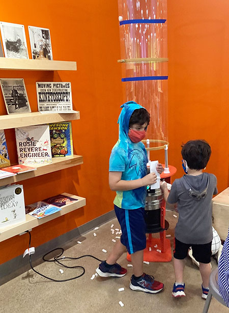2 young boys in front of a plastic vertical wind tunnel