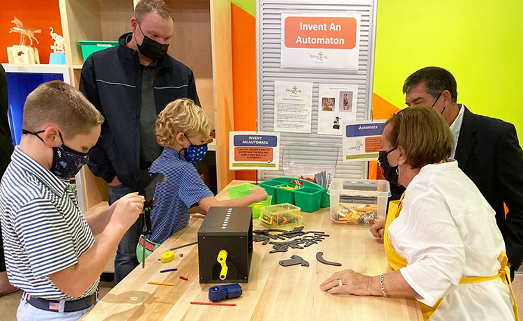 2 young boys, 2 adult men, and a woman facilitator work on inventing an automaton