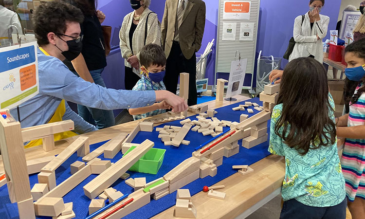 2 young girls, a young boy, and an adult man link wooden ramps together to build a marble run