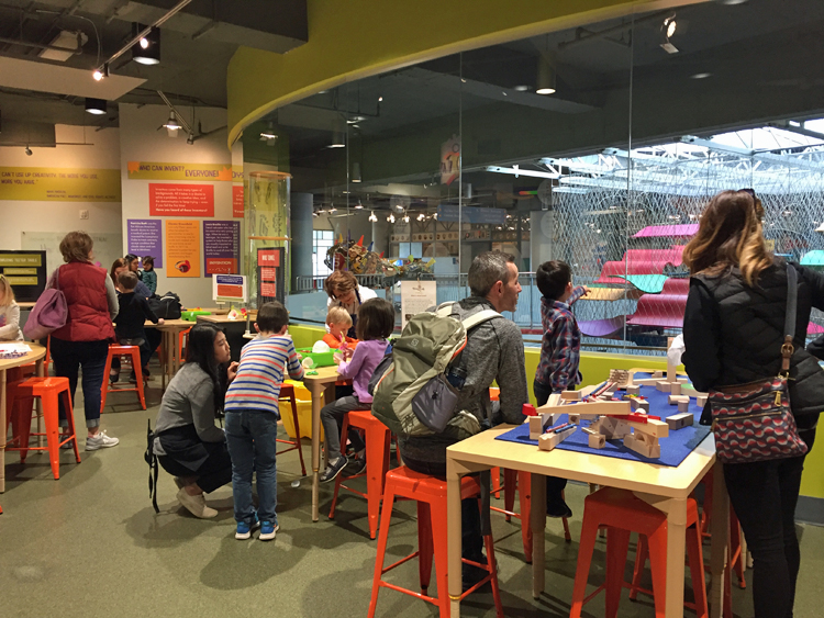 Families working at various activity tables in SparkLab at the Children's Museum of the Upstate