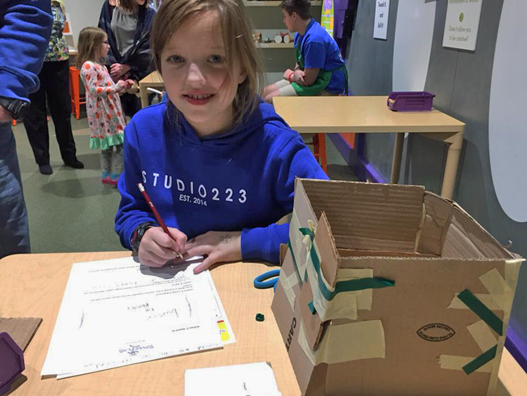 A young girl works on her invention