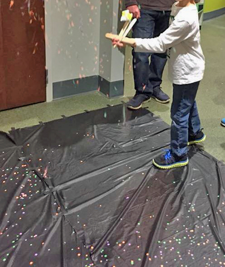 A child launches confetti from a device he invented.