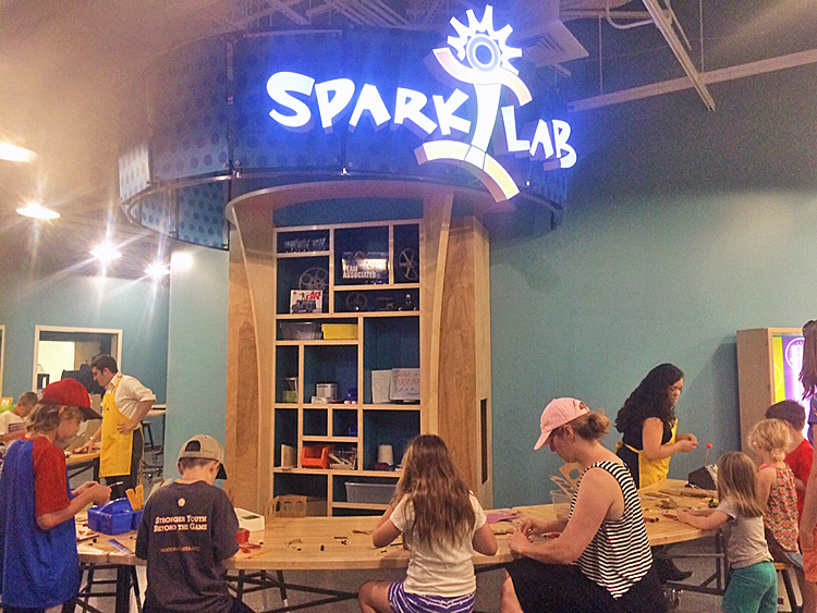 6 children and 1 adult work at an activity in the SparkLab Hub, assisted by 2 SparkLab facilitators