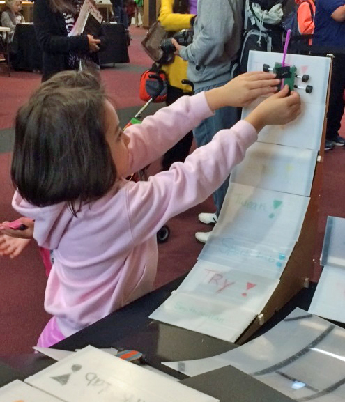 A young girl participates in a Spark!Lab activity
