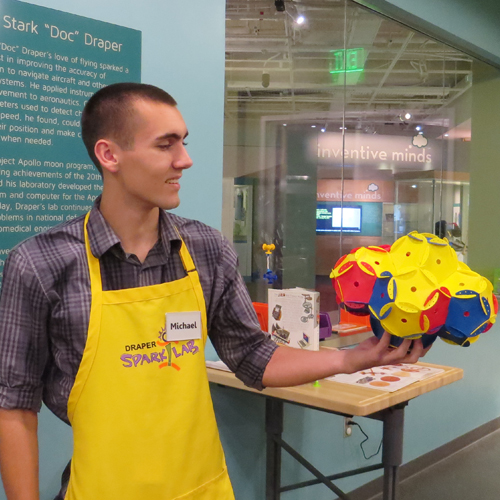 SparkLab volunteer in his yellow apron, holding completed activity