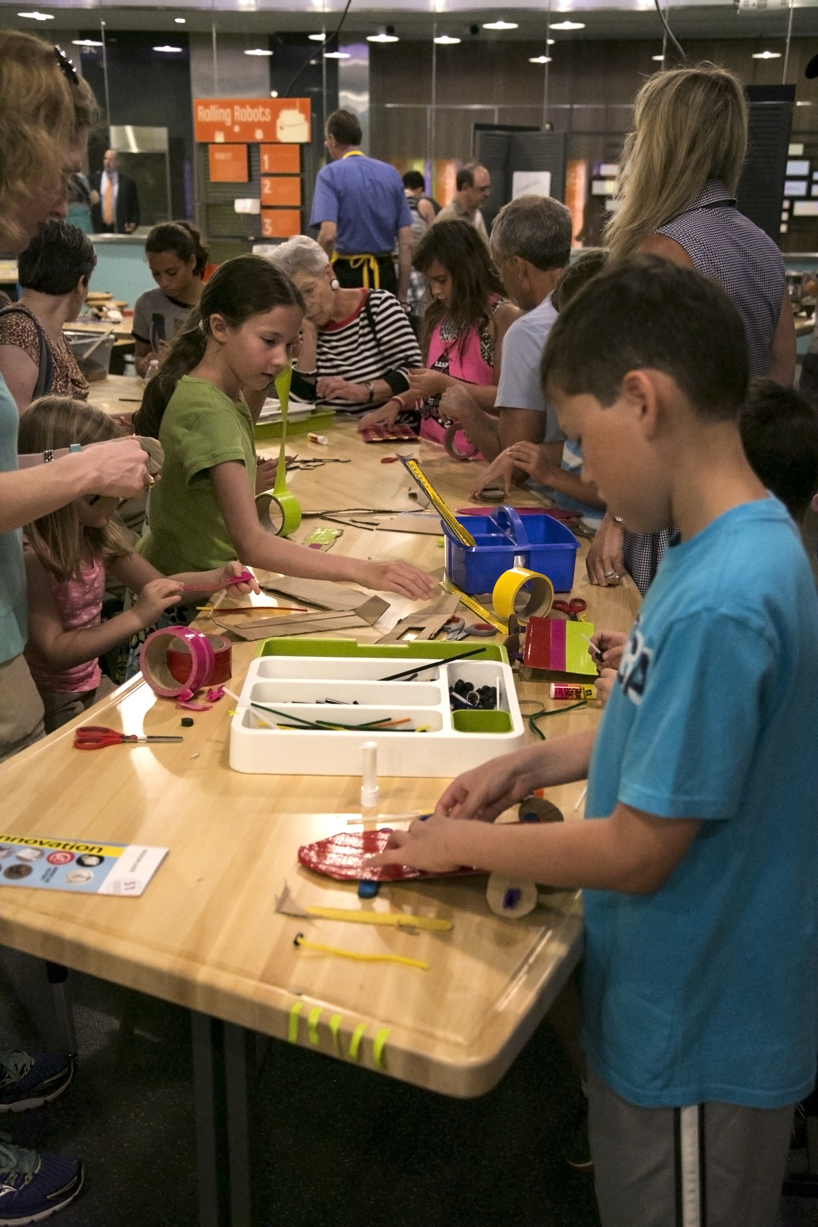 A crowd of about 30 children and adults work on activities in SparkLab