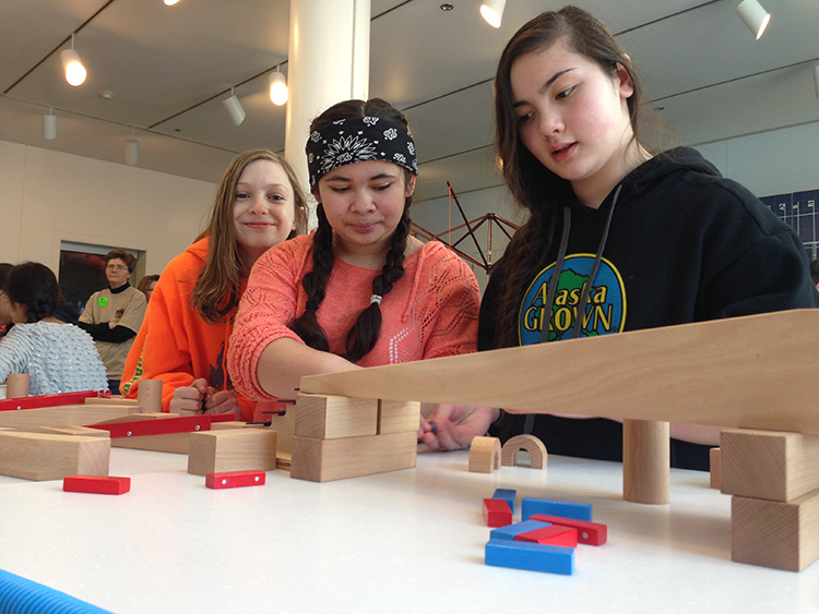 A group of girls collaborating during an invention challenge in SparkLab at the Anchorage Museum