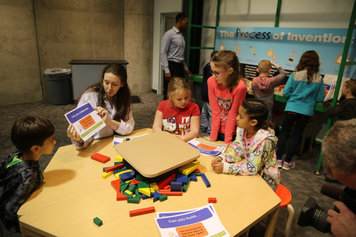 A facilitator works with children on an invention activity at Spark!Lab at Michigan Science Center