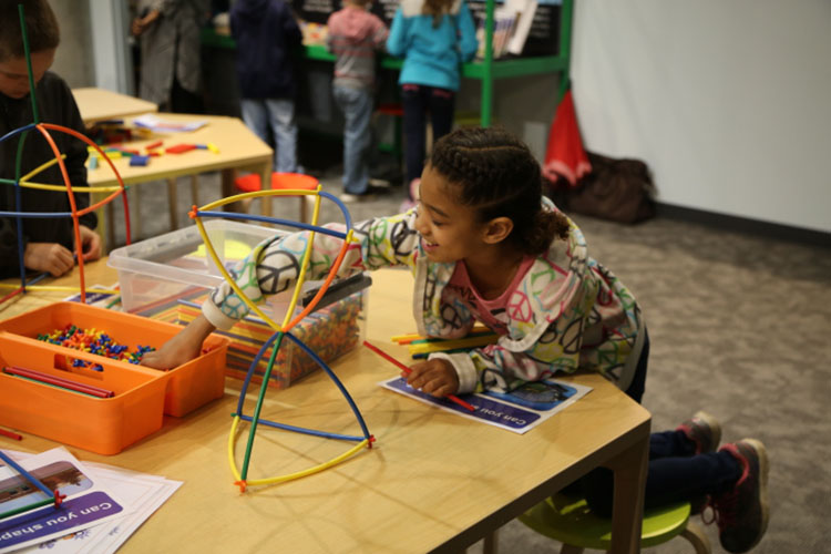 A young girl works on a Spark!Lab activity (Michigan Science Center)