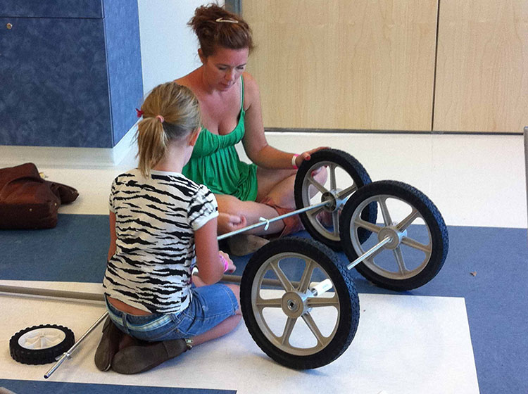 A mother and young daughter invent a vehicle using PVC pipe and wheels in Spark!Lab at the Terry Wells Nevada Discovery Museum