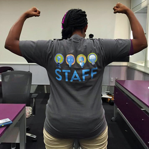 "SparkLab volunteer showing off her new tee shirt that reads ""Staff"""