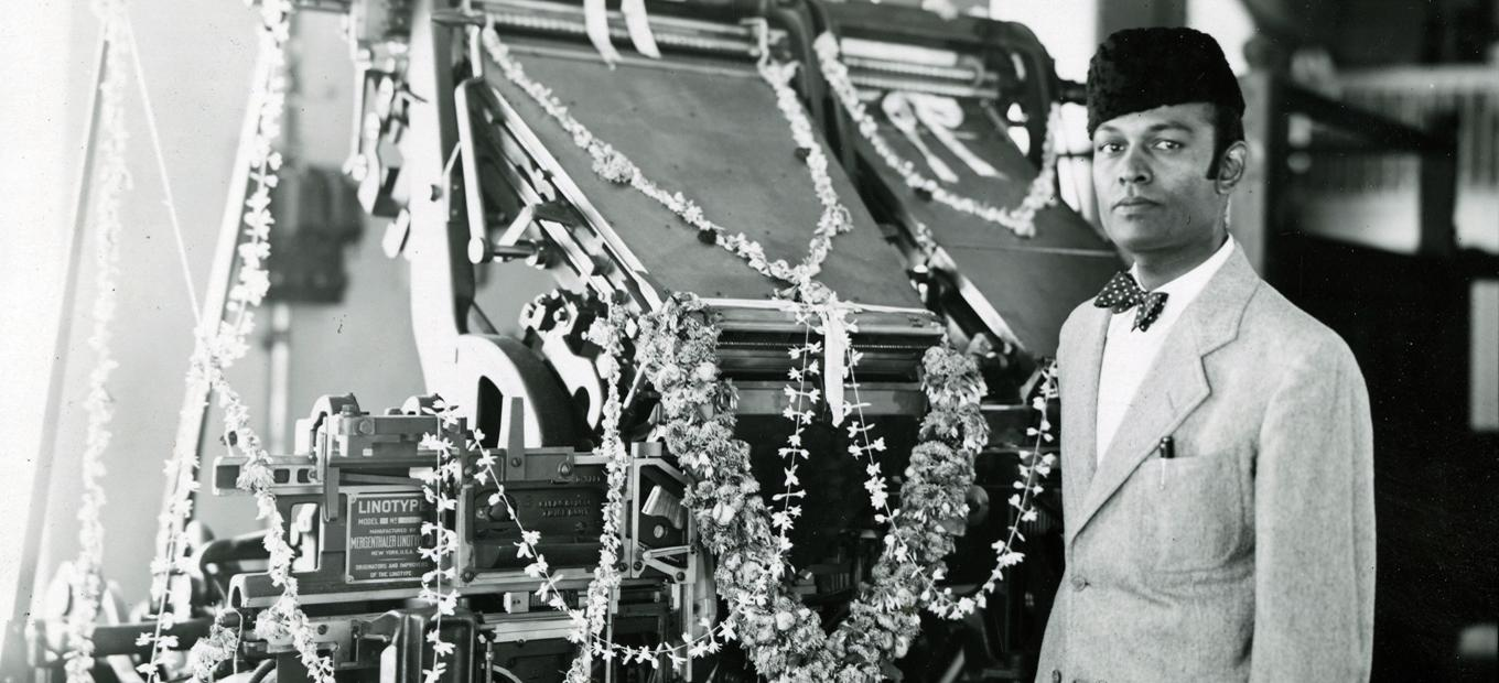 Hari Govil, wearing a sports jacket and bowtie, and a Karakul-type hat, stands in front to a Linotype machine festooned with flower garlands.