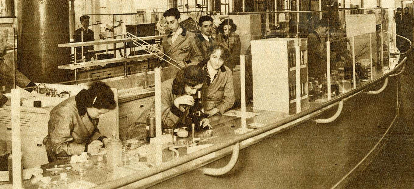 A group of male and female students and faculty in lab coats at different stations in a science lab at the Westinghouse Fair World, 1940. Some are looking through microscopes, others at models of airplanes, still others at biological specimens.