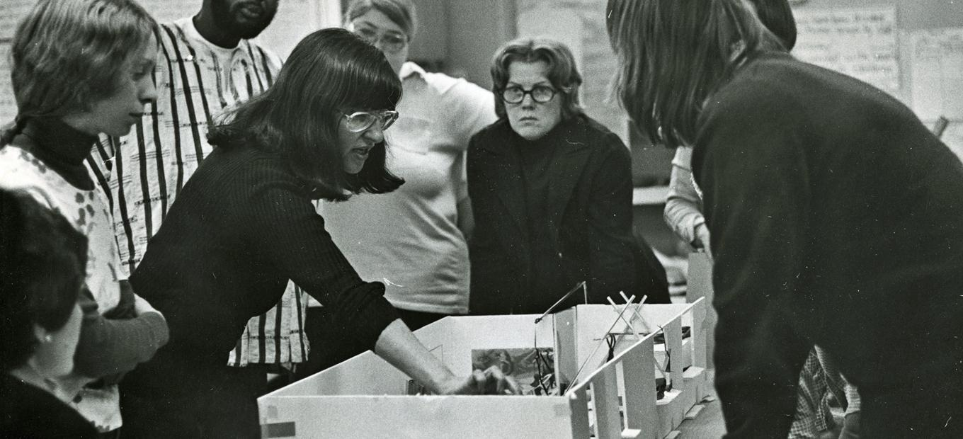 Elaine Ostroff, pointing at a model of a play room, with 6 staff members of Planning for Play around her, about 1975