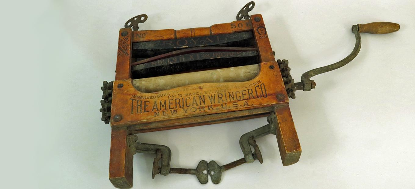 Color photo of a clothes wringer, comprised of two rubber rollers in a wood frame with metal gears, clamps, etc.