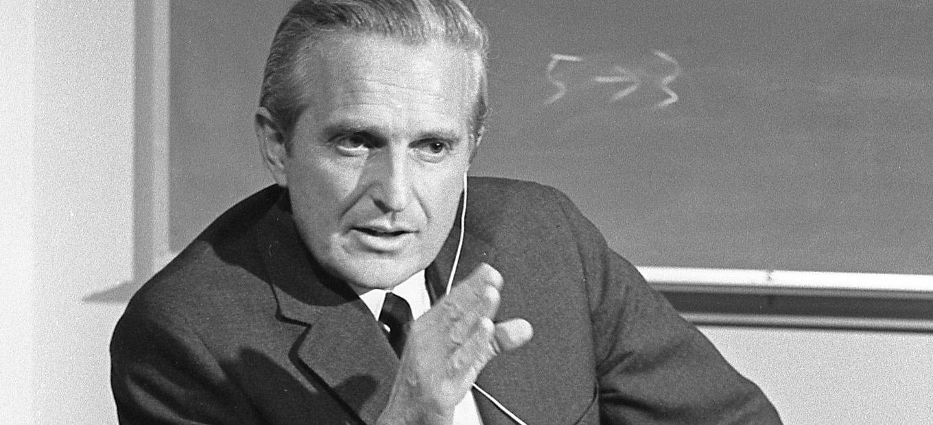 Douglas Engelbart in October 1968. He wears a jacket and tie and has a wired earpiece in his left ear. He is gesturing with his right hand and looking at someone off camera to his left. He is in front of a blackboard with the numbers 5 and 3 written on it; an arrow points from the 5 to the 3.