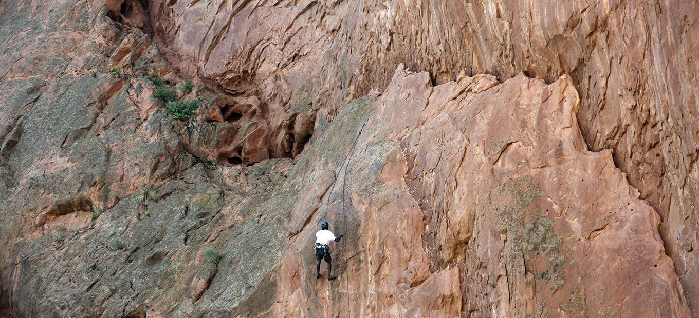 A lone rock climber scaling a red rock wall