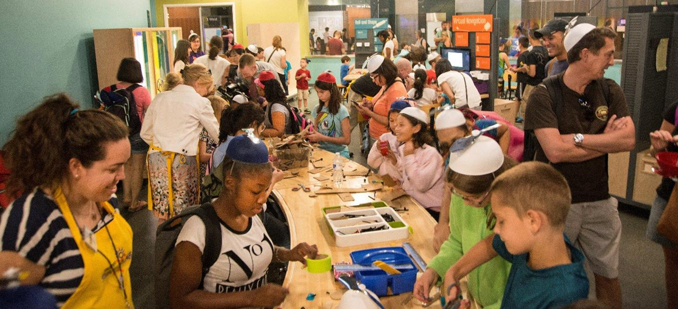 A very crowded overview of Spark!Lab, taken from the rear of the room and looking towards the entrance. This photo was taken on opening day, July 1, 2015, and visitors are wearing the propeller beanies that they received as gifts from the museum.