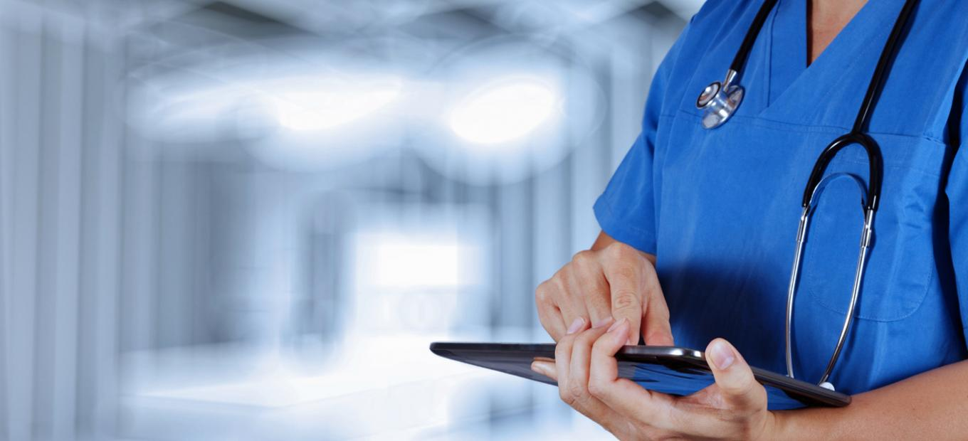 Female health professional with tablet computer, stock photo via Shutterstock