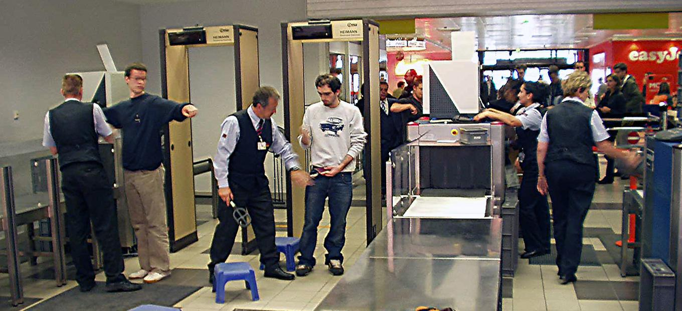 People passing through metal detectors and baggage x-ray at an airport