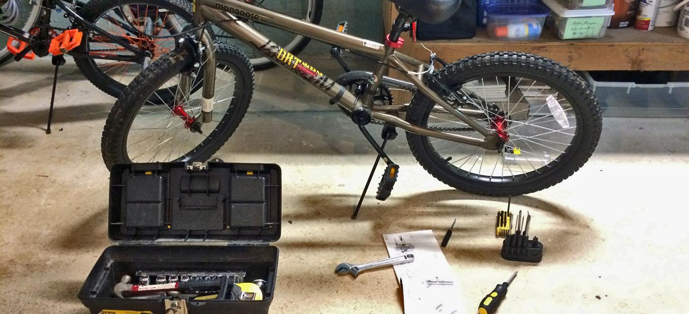 The author has set out the tools and instructions needed to repair his son's bike on the garage floor in front of the bike