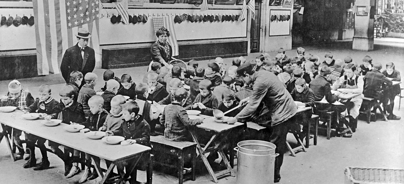 Approximately 70 boys around 8-10 years of age seated at long tables outdoors and receiving food from a man and a woman while another well-dressed man looks on