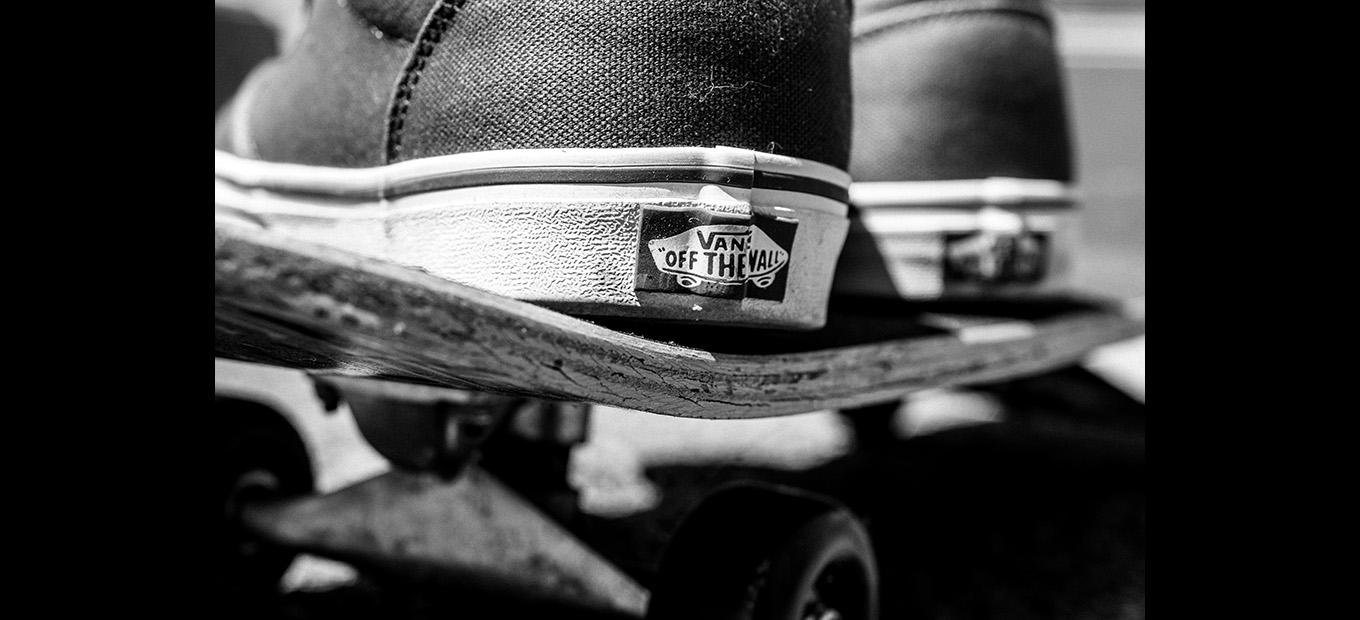 Close-up of the heel of a skateboarder's shoe, showing the Vans label, on a skateboard