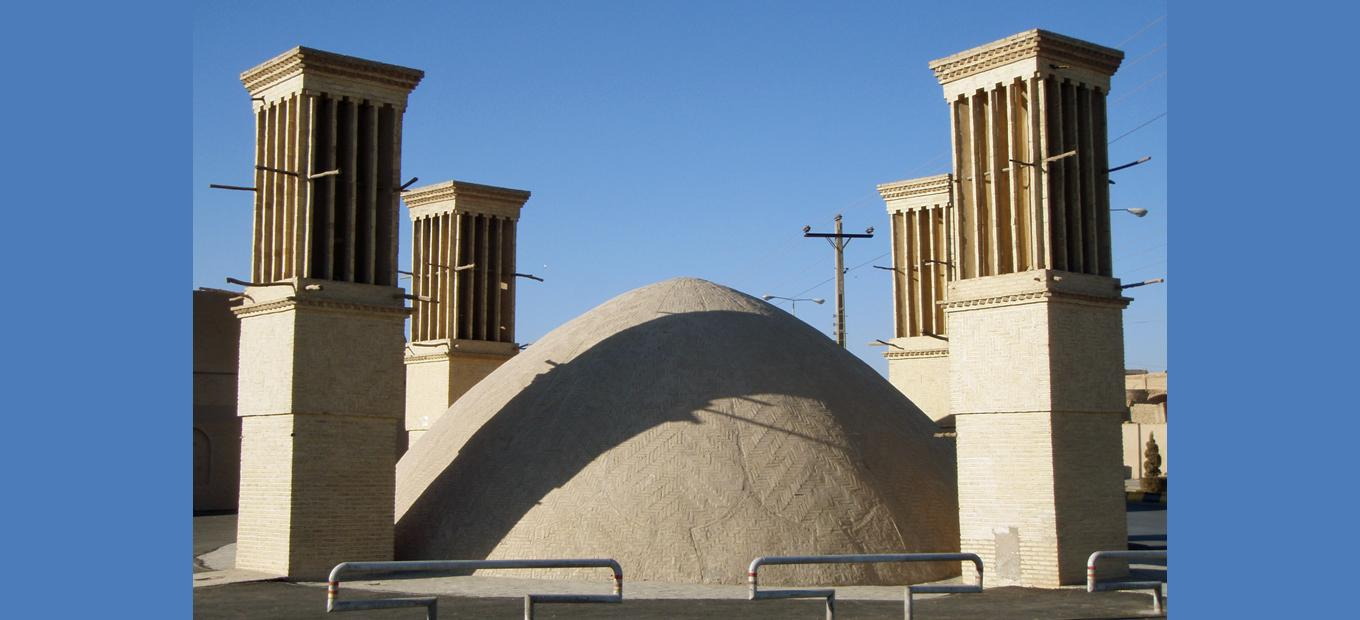 4 wind towers and a domed structure that covers a reservoir of water