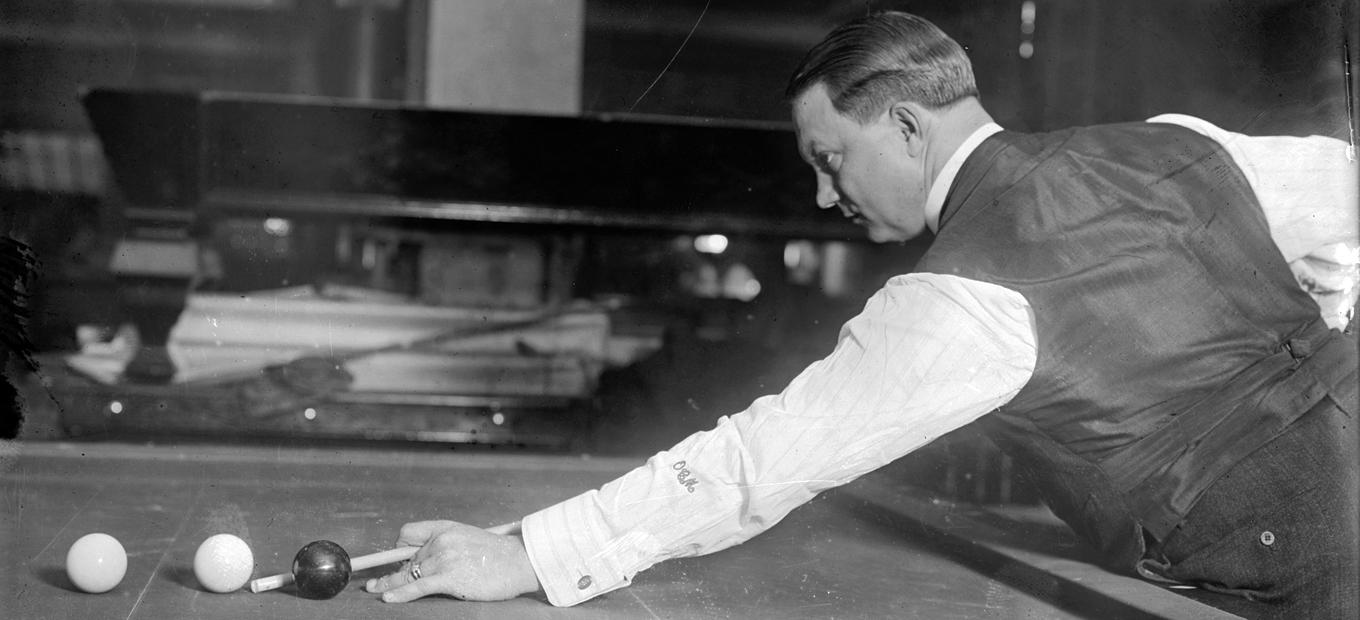 Side view of billiards great Ora C. Morningstar, bent over billiards table, cue stick in hand, about to take a shot.