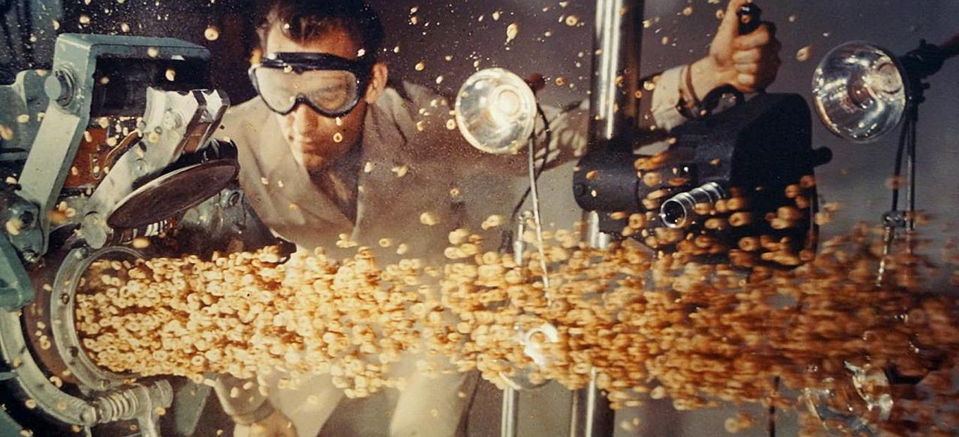 A man wearing a lab coat filming the puffed grain as it emerges from the puffing gun, undated