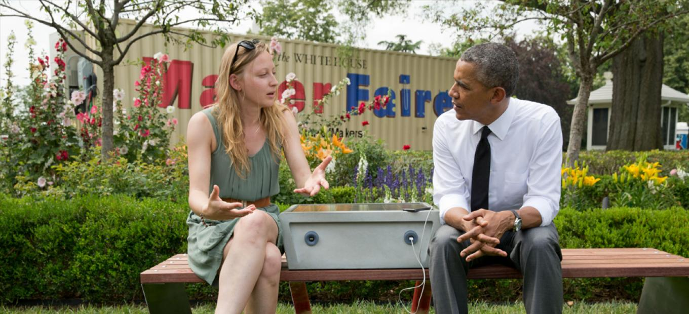 President Barack Obama chats with inventor Sandra Richter, whose solar-powered park bench allows users to charge their mobile devices.
