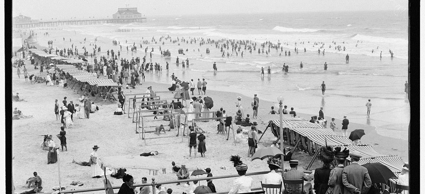 Black and white photograph of crowds on the beach in Atlantic City, NJ in 1908.