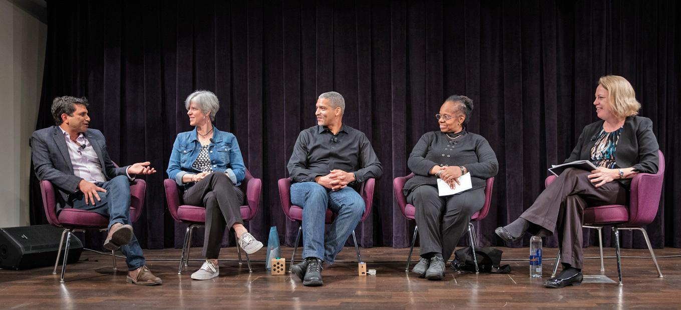 Panelists in chairs on stage