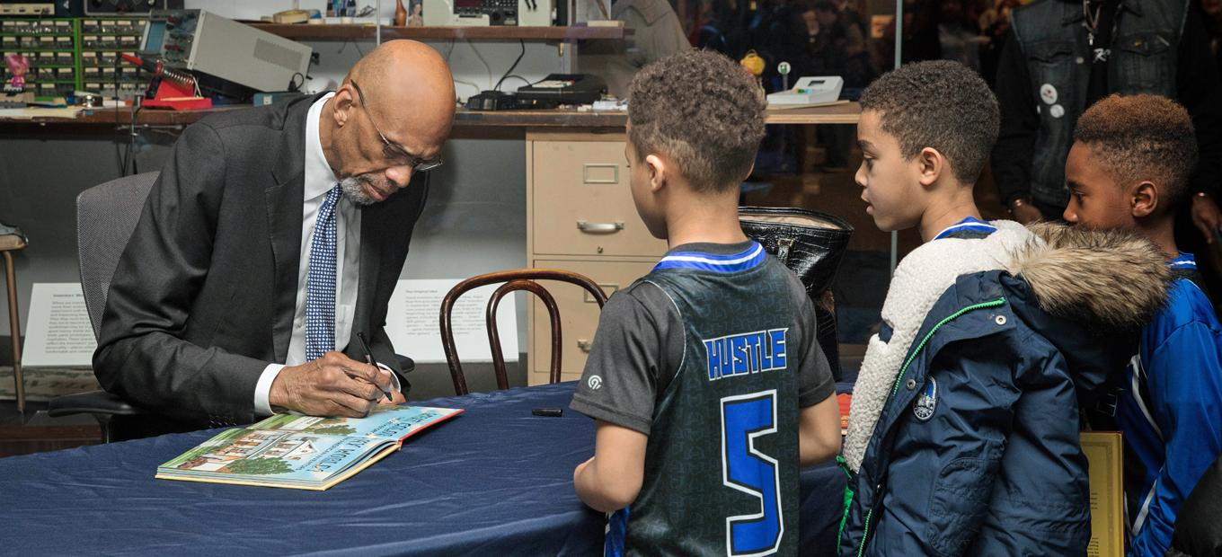 Kareem Abdul-Jabbar signing books for 3 young boys