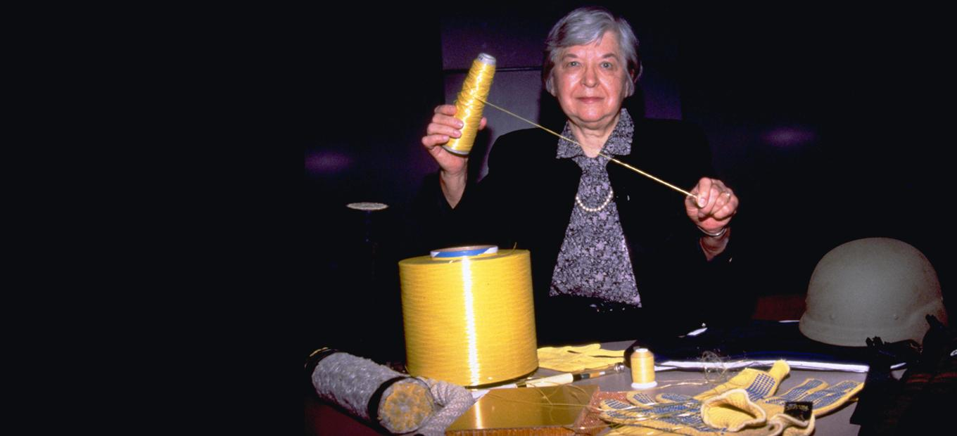 Stephanie Kwolek holding up a thread from a spool of Kevlar