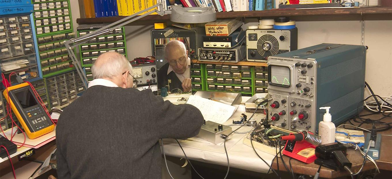 Ralph Baer sitting at his work table, with his back to the camera, working on something.
