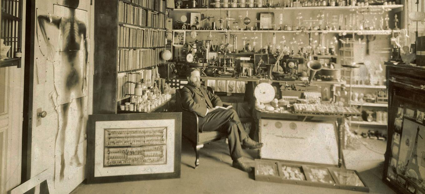 William Hammer seated in a room cluttered with scientific and experimental apparatus, including phonographs and Leyden jars