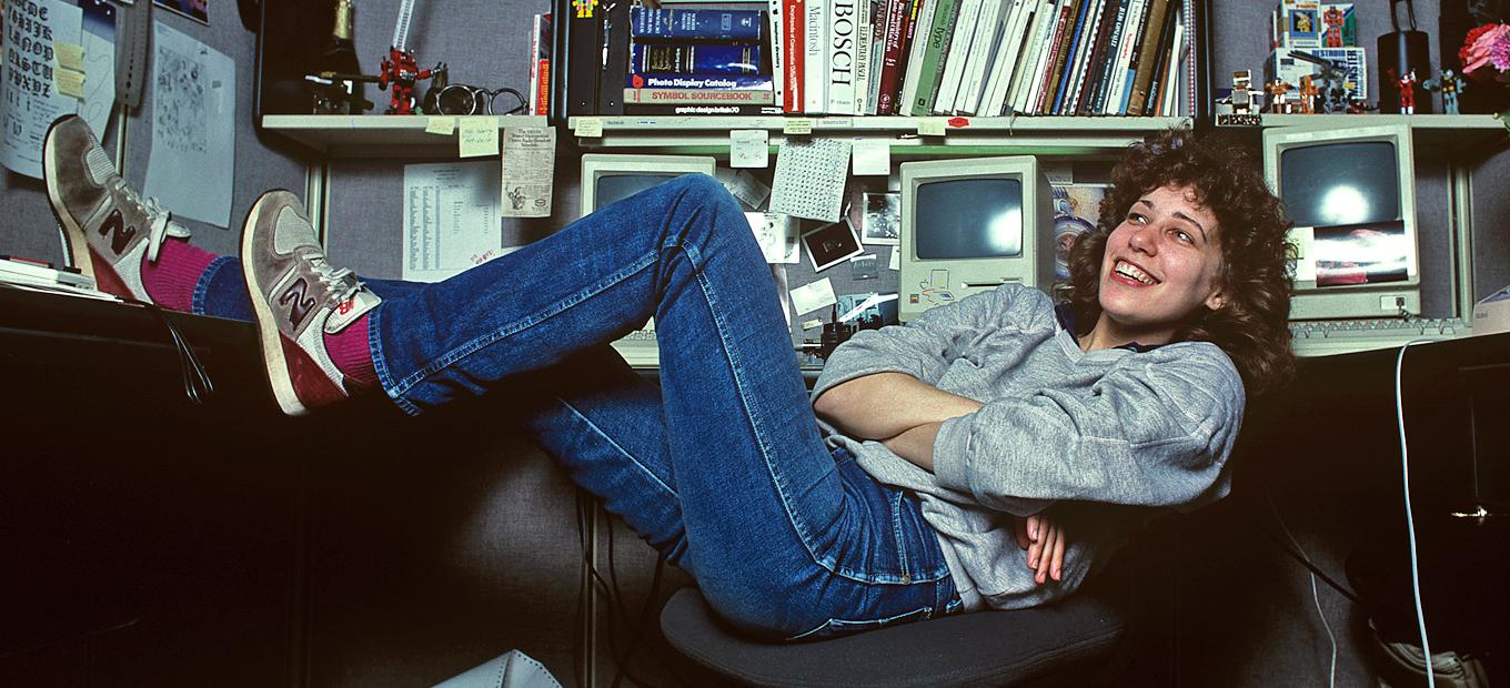 Side view of Susan Kare, seated tilted back in a desk chair with her legs stretched out. To her right, there are bookshelves and a desk, with books, 2 Macintosh computers, and many other items.