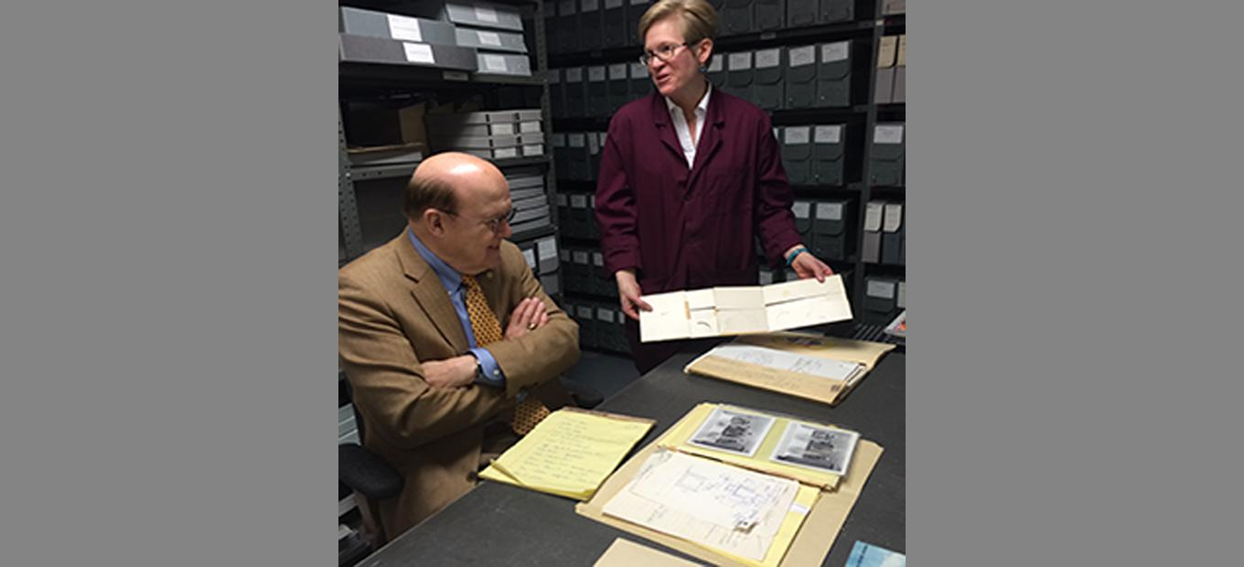 Inventor Manny Villafana seated at table; archivist Alison Oswald standing and showing archival materials to Villafana