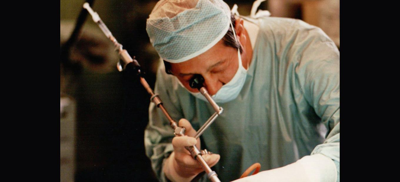 Close-up of Dr. InBae Yoon wearing a surgical gown, cap, and gloves, using a laparoscopic surgical tool. The patient is not visible in the photo.