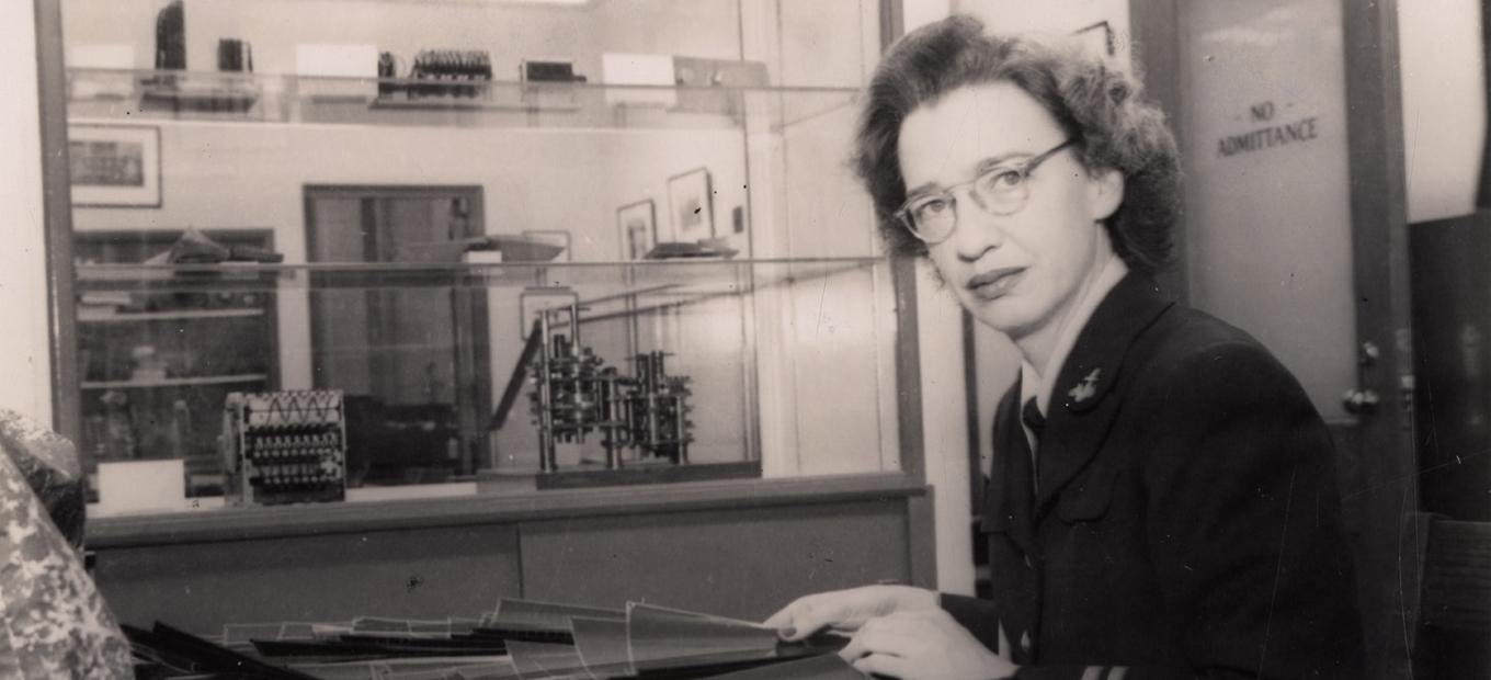 Lt. Grace Hopper at her desk in the Computation Laboratory. Glass shelves with early calculating machines seen in background, 1947.