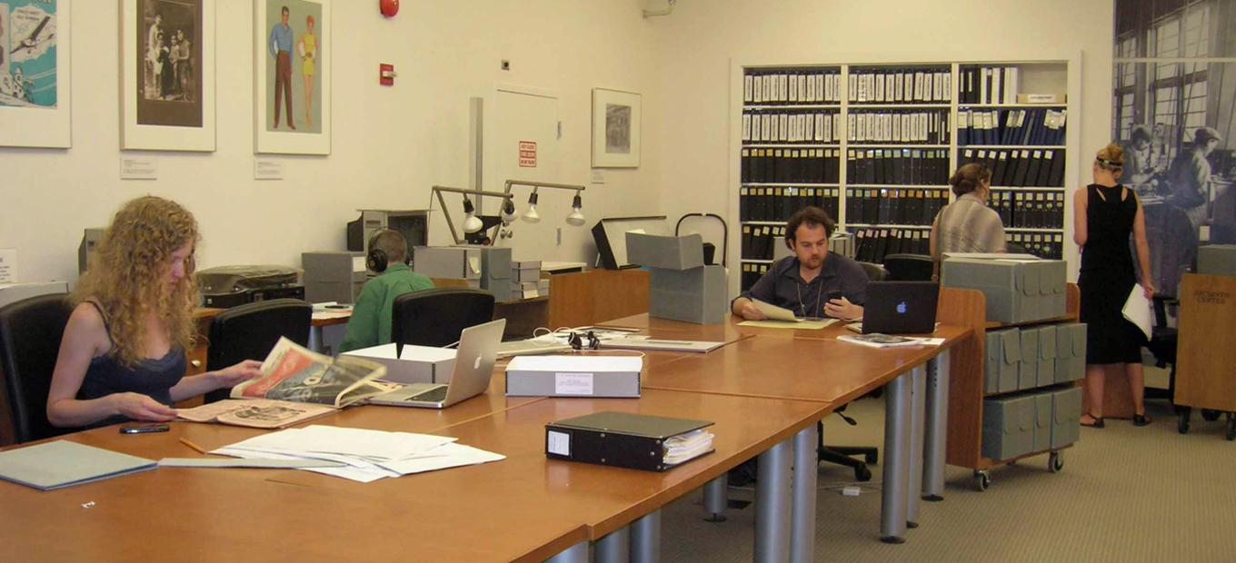 Archives Center reading room with large tables and people doing research. Lemelson Fellow Hallie Lieberman sits at the far left and fellow Matthew Hockenberry sits at the center of the photo.