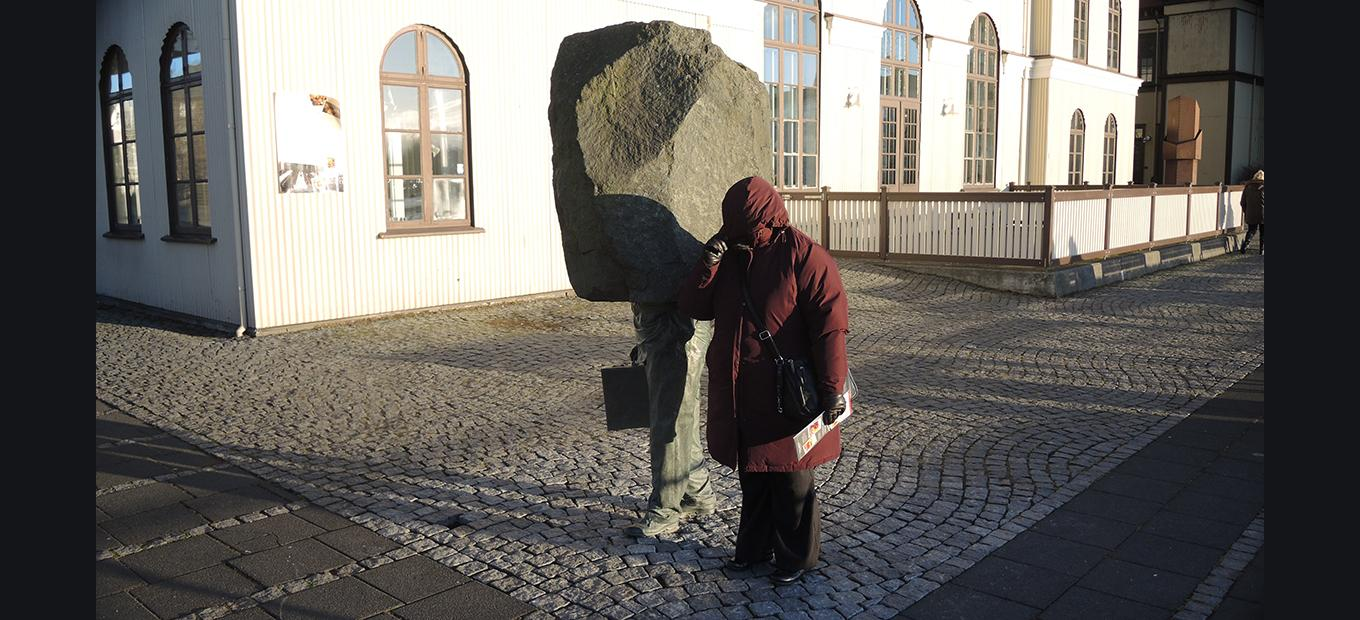 Woman in a winter coat standing next to a sculpture of a businessman whose head is a block of stone