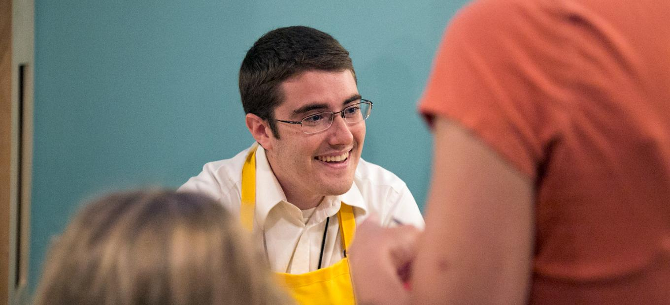 A smiling Zach Etsch is seen over the shoulders of an adult woman and young girl, visitors to SparkLab during its press preview in 2015. He is smiling and wearing his yellow SparkLab apron.