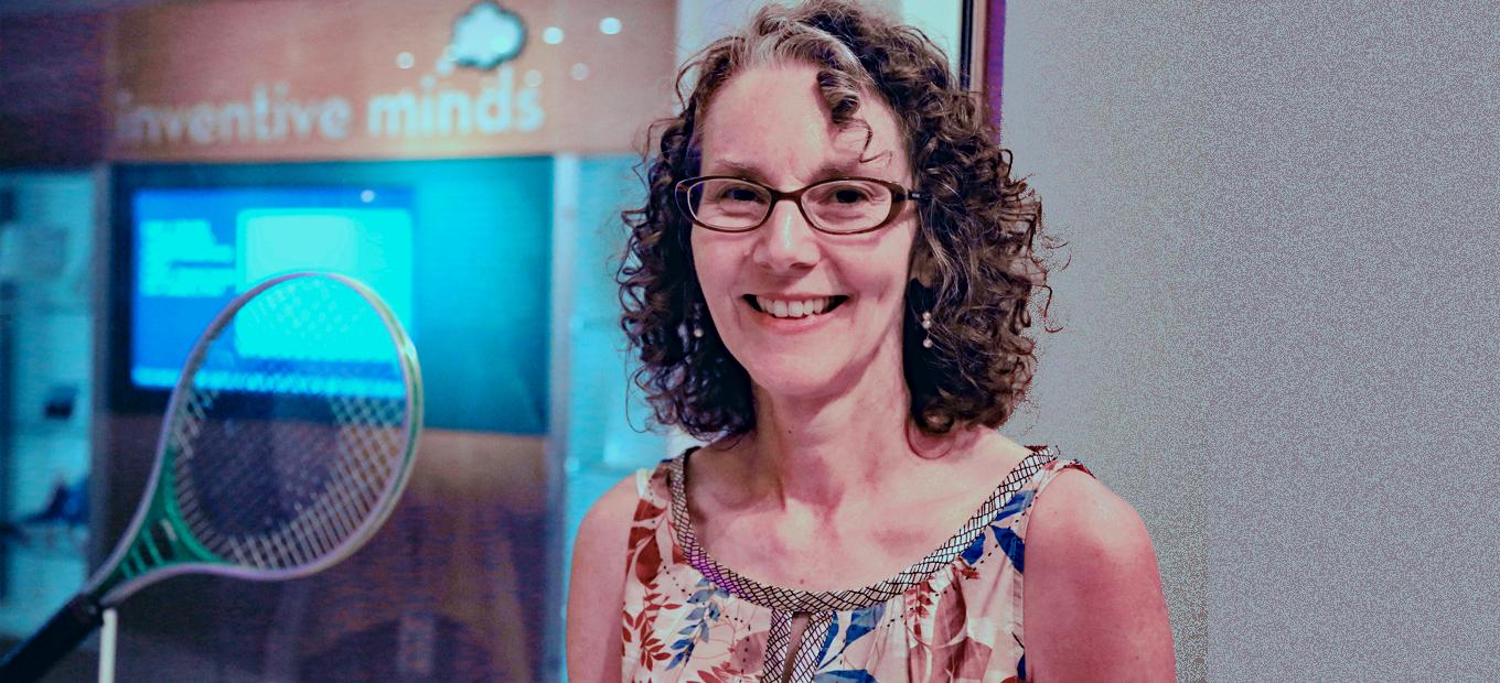 Head-and-shoulders shot of Meg Maher standing outside the Lemelson Center's Inventive Minds gallery. A tennis racket is visible in the exhibit case to her right. She has shoulder-length curly brown hair and wears glasses. She is smiling at the photographer.