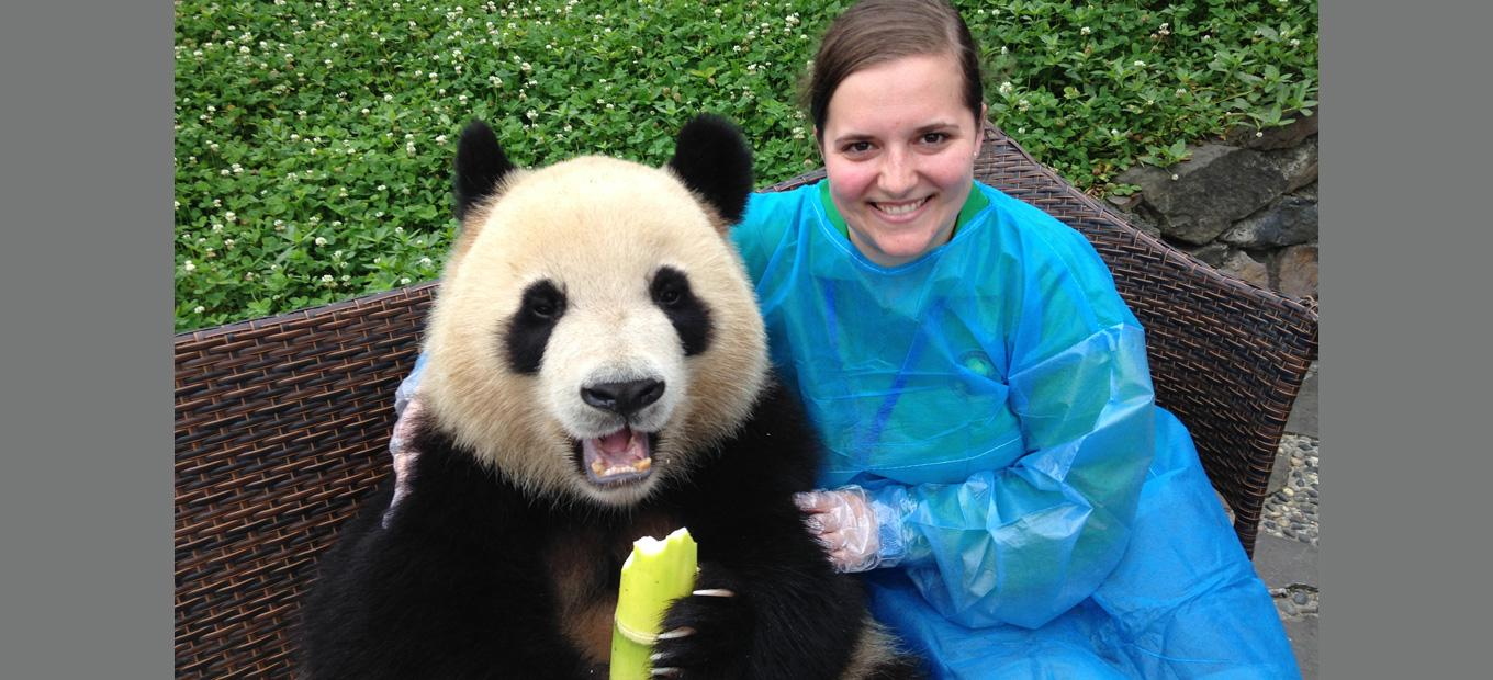 Abigail Phelps sitting on a bench with her arm around a live panda