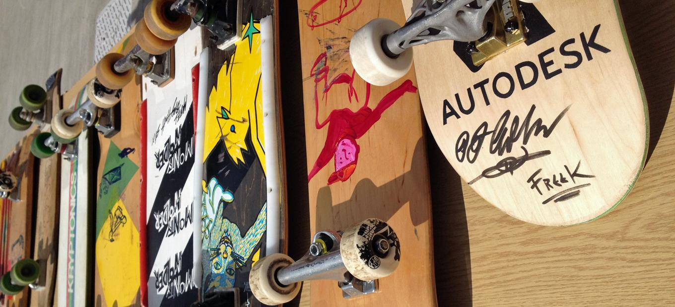 A row of 8 skateboards, deck down, showing the addition of artwork over time; the oldest boards are plain wood.
