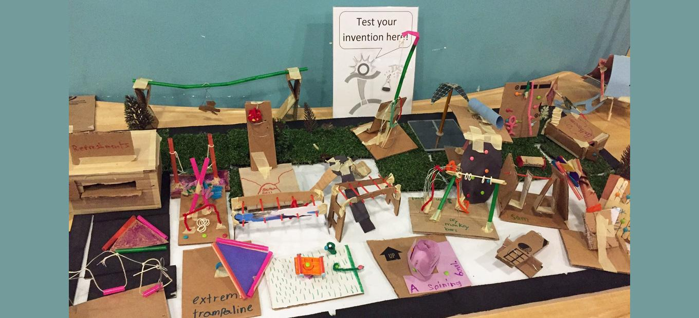 A table covered with kids' inventions made with cardboard and other craft materials