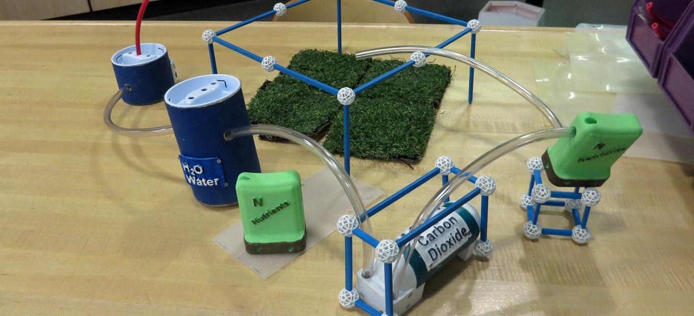 5 plastic containers marked H2O, carbon dioxide, and nutrients are connected by plastic tubing to nourish four small square of grass, in a prototype for a Mars garden