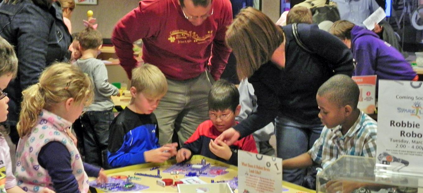 2 adults and several children are at a table, working on an activity in SparkLab.